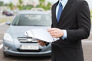 Auto insurance agent in front of car