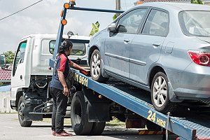 Man loading blue car onto tow truck