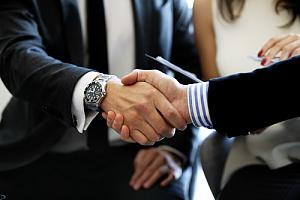 Future executive shaking hand of current executive