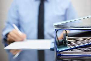 Person with binders and paperwork on desk