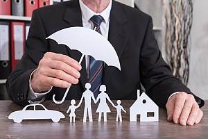 Man holding paper umbrella over personal insurance items