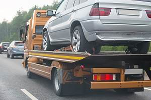 Tow truck with car on highway