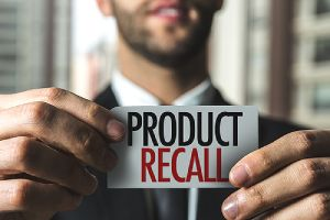 A man holding a card that has Product Recall written on it emphasizing Product recall insurance
