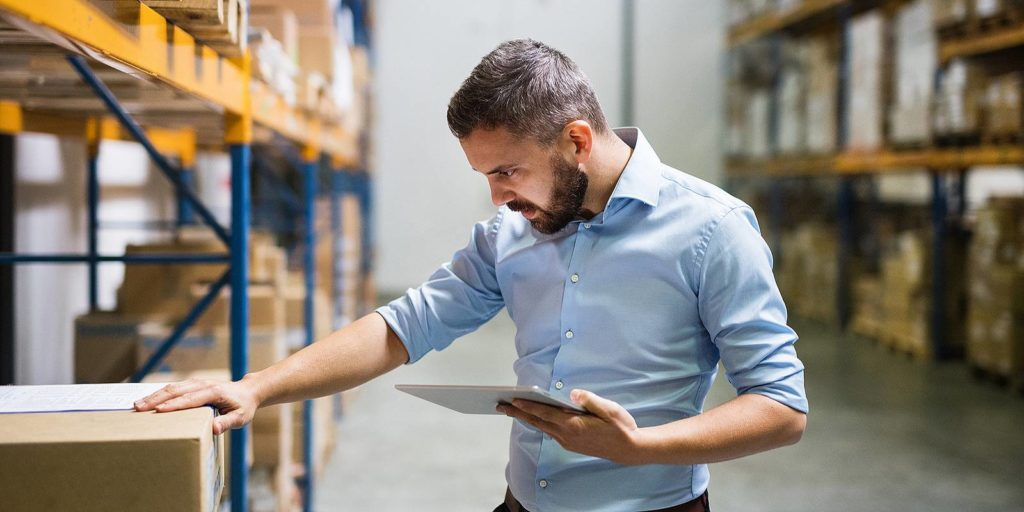 A worker in a warehouse checking products holding a tablet. Product recall insurance can protect Business owners