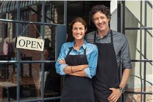 Two cheerful small business owners standing at entrance door.Know the Insurance Needs for your Business