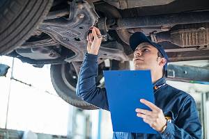 a mechanic inspecting an auto mobile in an auto mechanical repair shops. towing insurance also covers roadside repairing.