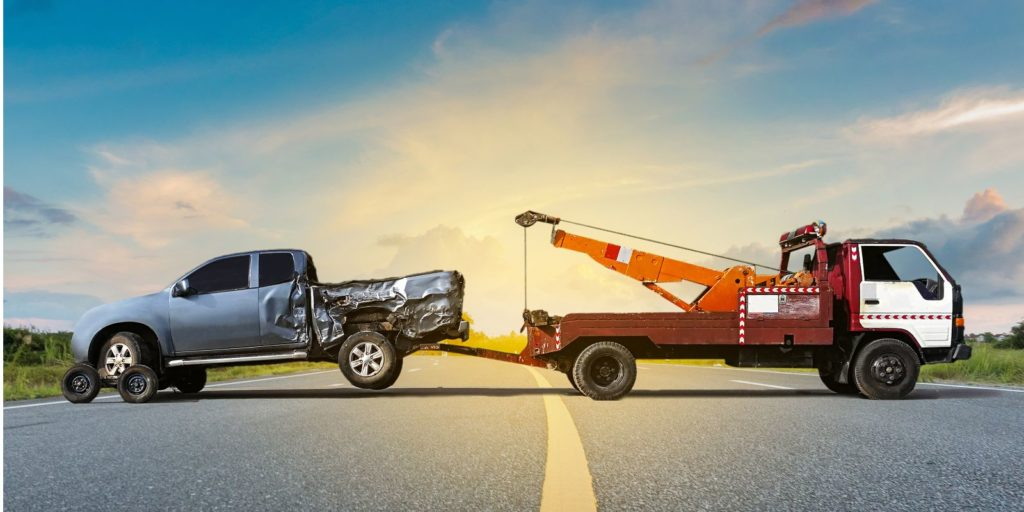 a tow truck towing a damaged truck in the middle of a road. Towing insurance can be very helpful for tow truck business owners