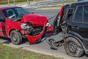 damaged automobiles that need towing after collision on a street.