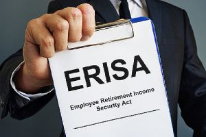 An employer holds a clipboard that has employee retirement income security Act or ERISA