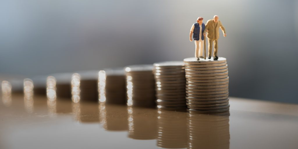 Figurine of older couple standing on top of coin stack. ERISA encompasses employer that provide pension plan