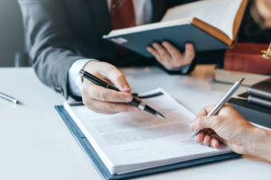 person signs fiduciary liability insurance contract after talking to insurance agent