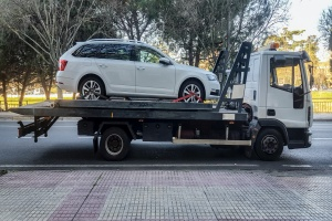 Station wagon car being towed by a tow truck with On-Hook Towing Insurance