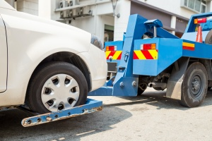 Tow truck towing taking a while car with On-Hook Towing Insurance