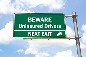Green overhead road sign. Towing insurance coverage pays for injuries to you and your passengers caused by drivers