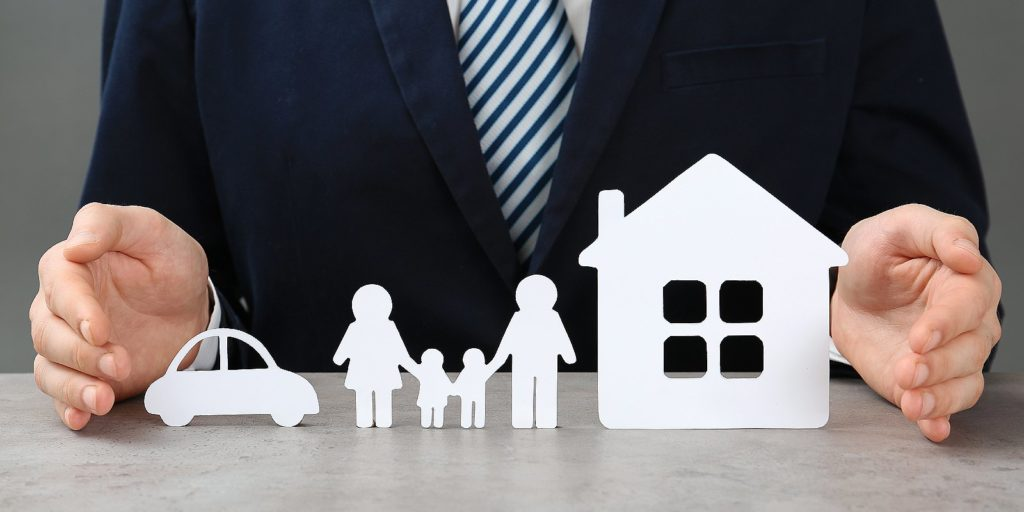 Man with cutout paper family, house and car, HOA Insurance concept. Condo associations also need HOA insurance