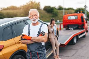 Towing service provider standing in front of his truck. Towing business requires tow truck insurance