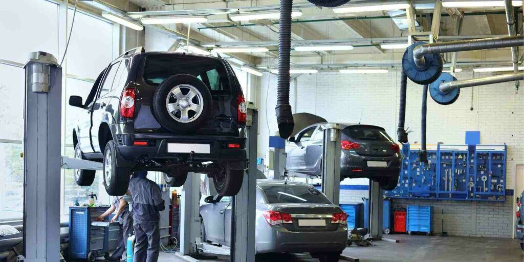 cars in small service station and two men repair one car