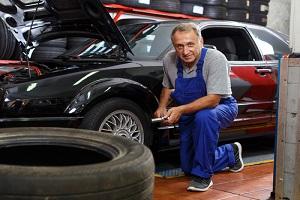 mature man car mechanician changing car wheel in auto repair shop