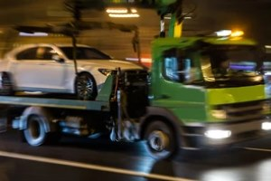 green truck towing white car