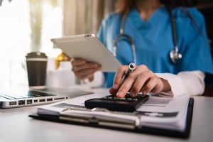 physician with stethoscope calculate medical fee costs with medical payments coverage