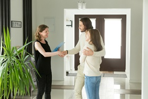 friendly realtor and young couple shaking hands after knowing the Cost Of Landlord Insurance