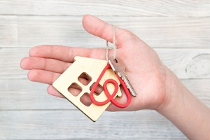 key to the apartment or house with the key pendant in the form of the logo with landlord insurance for airbnb