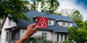 logo airbnb and the old beautiful house with green garden on the background